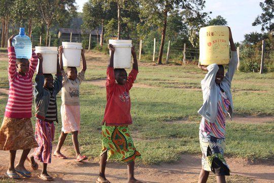 Our children carrying water from the stream