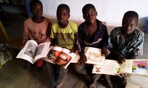 Reading children's books in Karaba library 2015