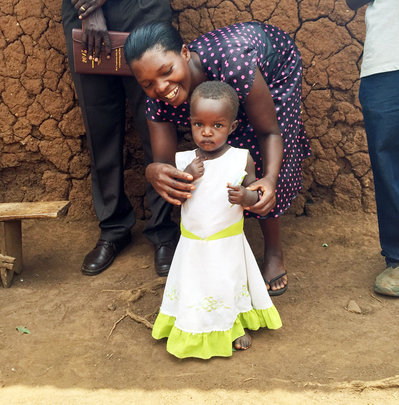 Little girl in Uganda w/ community health worker
