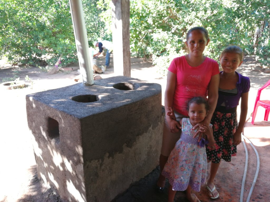 Mirelis and children stand by their new stove