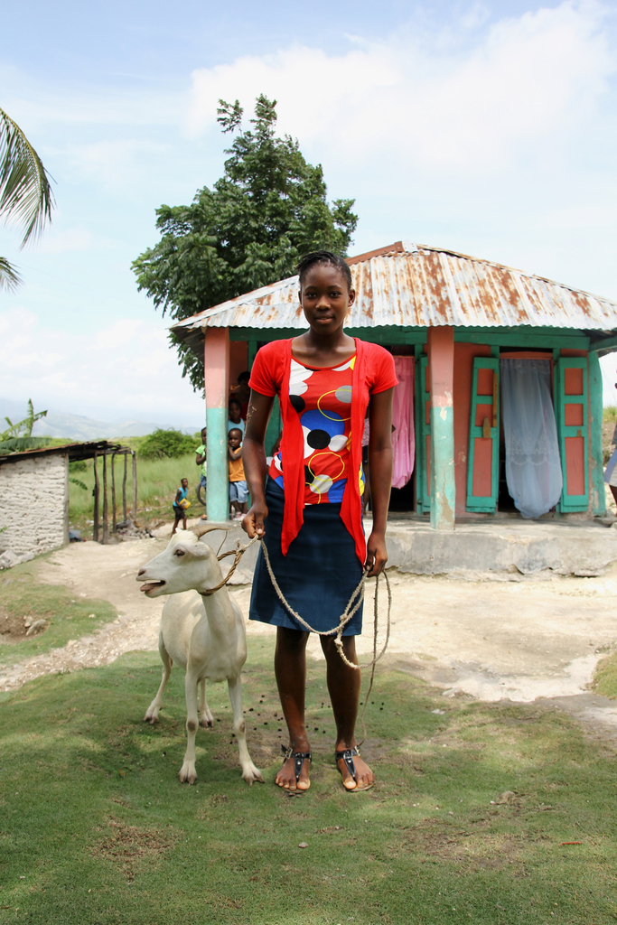 Encise with her goat in front of her home in Haiti
