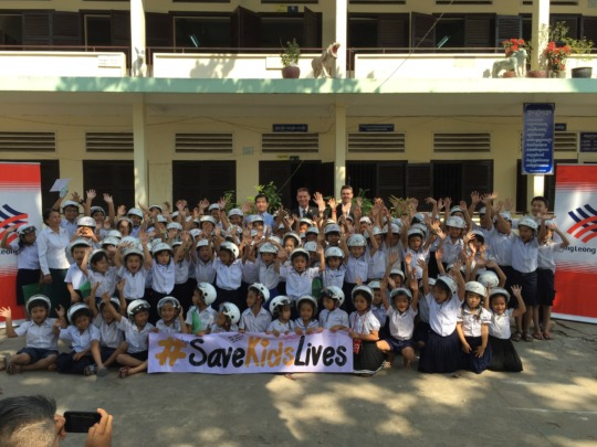 Students in Phnom Penh receive their new helmets.