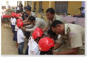 Traffic police fasten helmets on students