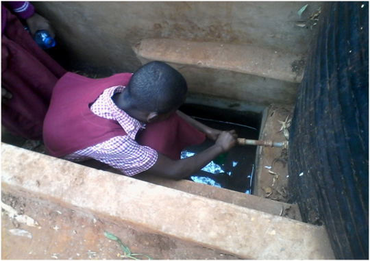 A pupil drawing drinking water from water tank