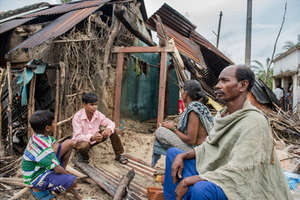 Basu Das and family in front of their damaged home