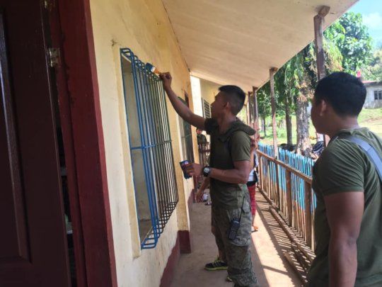 Soldiers help the community by helping to paint