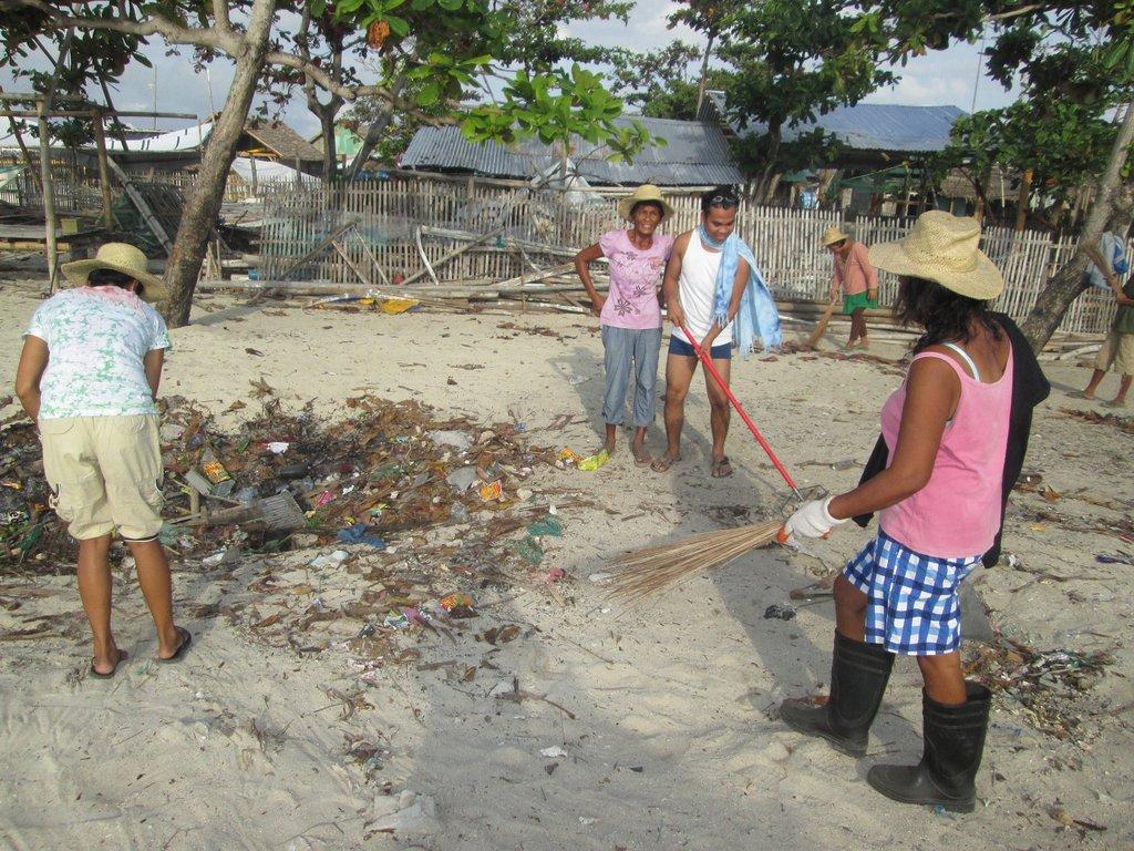 Baliguian island residents cleaning beach