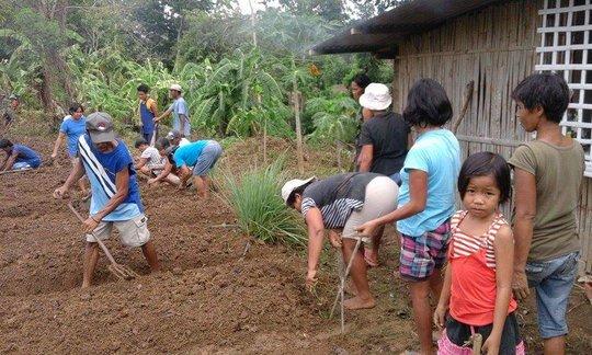 children help parent plant school-based garden