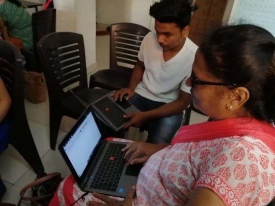 Deepa taking the exam alongside a young classmate