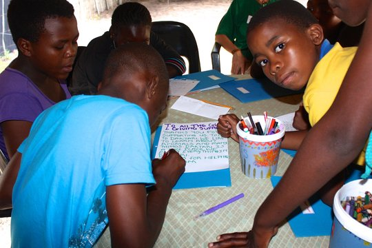 The children writing their thank you letter to you