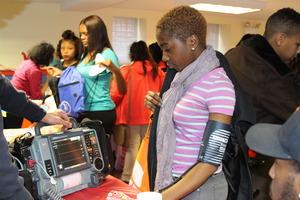Fair participant checking their blood pressure.