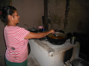 Isabel A. cooking on her improved cookstove