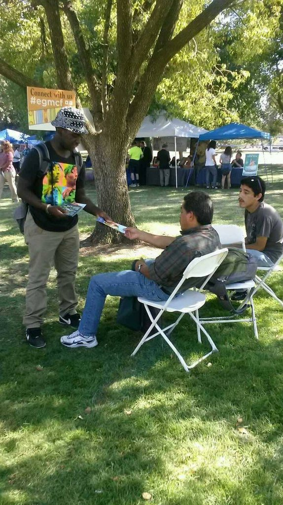 Kakari passing out flyers at a fair in Sacramento