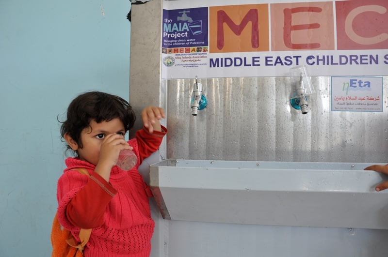 A child at Ajial Kindergarten drinks clean water