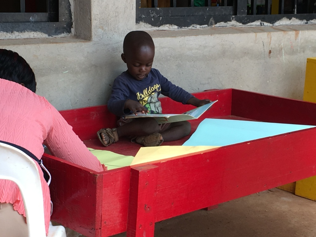 A child reads as the mother is doing her things