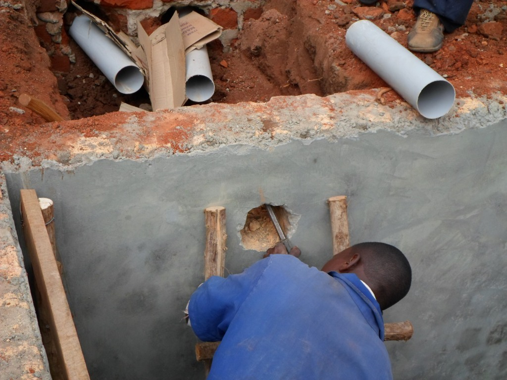 Plumber fixing the e swage system for the toilets
