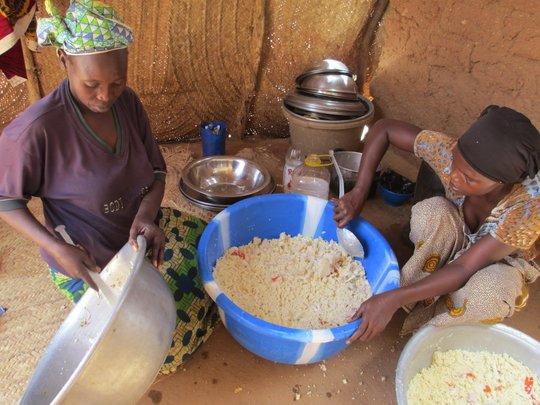 Women preparing couscous with vegetables