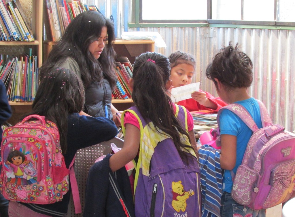 Alejandra helps girls check out books