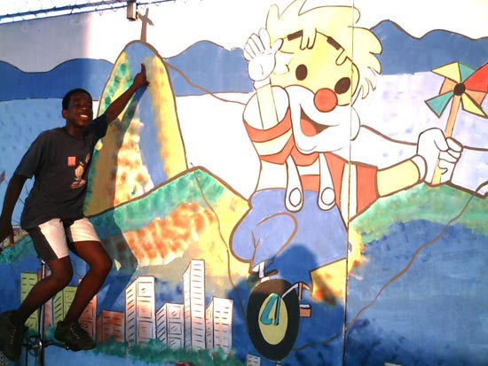 Youth on Unicycle with Mural at the Project