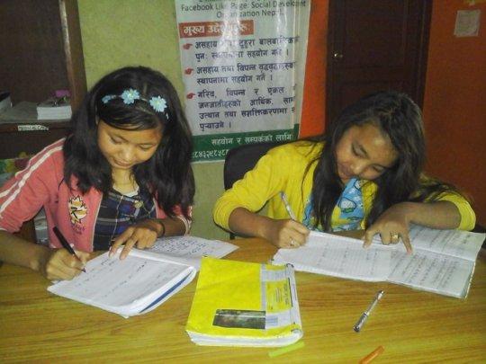 PRIYA,Class-7 and ANJU, Class-6 busy on homework.