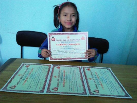 SRIJANA,Class-1 happily displaying certificates .