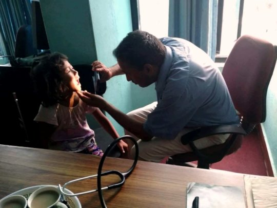 Dr. Thakur is on medical checkup to children.