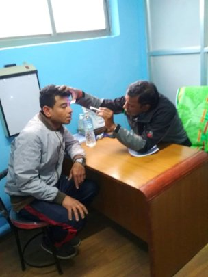 Dr. Triloki on health check up at health camp.