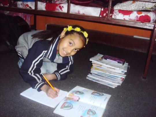 SARASWATI, Class-4, busy on home work.