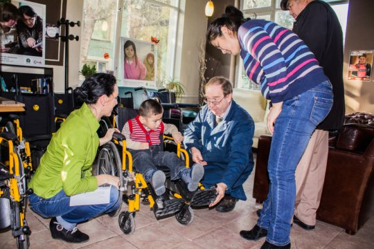 Giving away wheelchairs to kids with disabilities