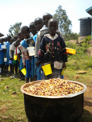 children lined up for lunch of maize and beans