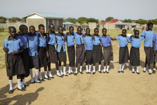 Schoolgirls pose for a picture at school in CES
