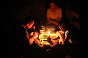 A family eating dinner together in semi darkness
