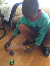 Agnes' son playing with toys in his new apartment
