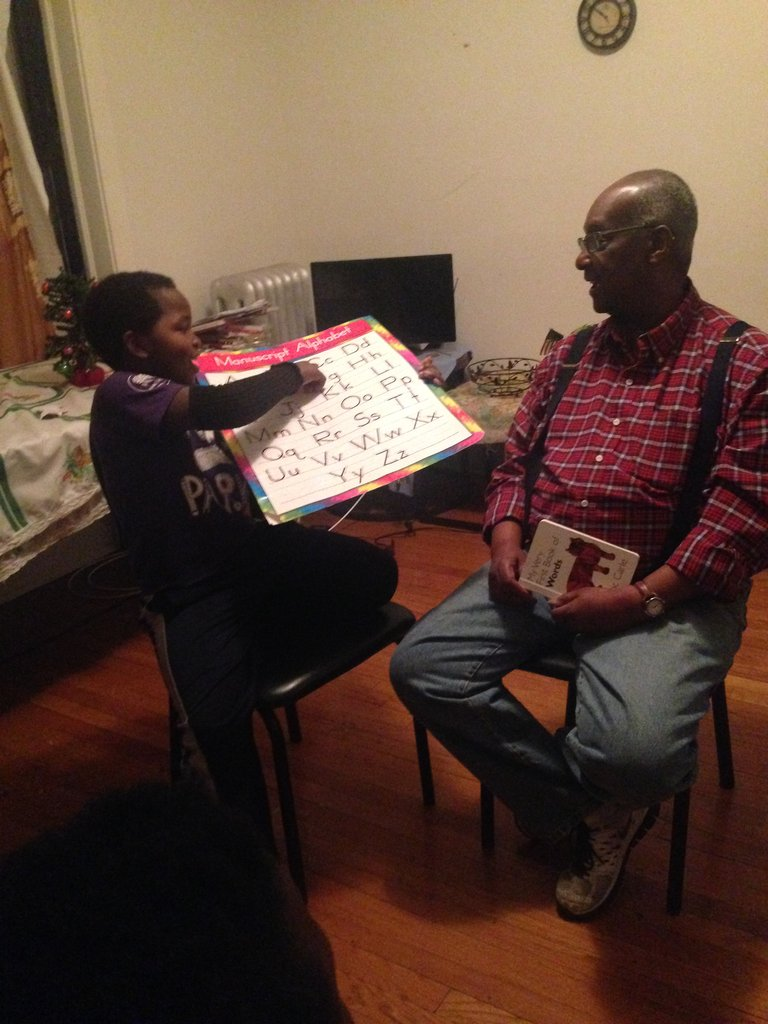 Emmanuel, age nine, practices English with Sherman