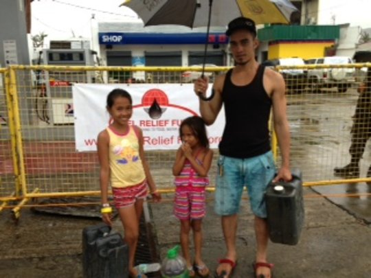 Family receiving fuel in Tacloban City