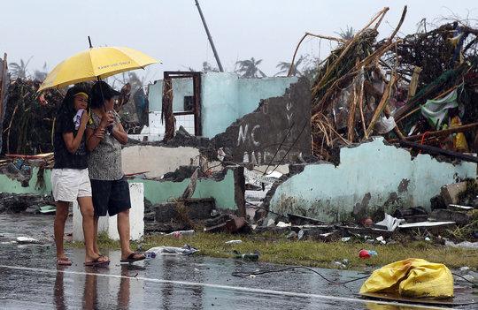 women share an umbrella - REUTERS/Erik De Castro
