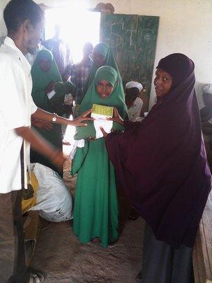 Student receiving Solar Lanterns and uniform