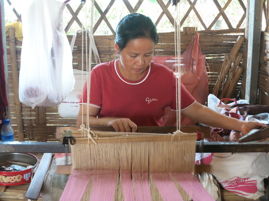 a woman from the camp weaves w/a loom from TBF