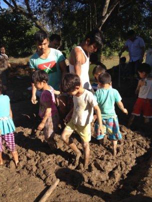 Kachin children in making mud bricks for school