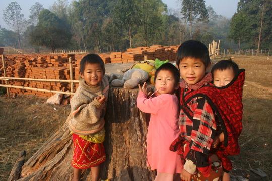 Kachin children playing near finished bricks