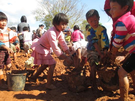 Kachin children helping to mix for mud bricks