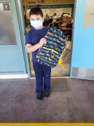 A little boy masked holding a colorful backpack