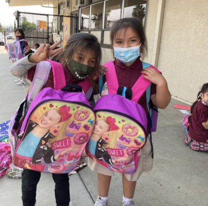 2 girls with their backpacks & making a peace sign