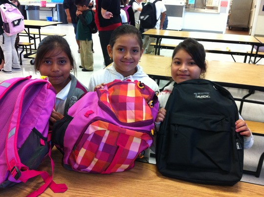 A trio of smiles and backpacks