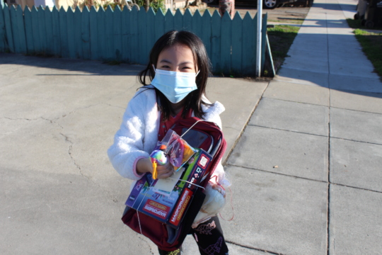 A little girl smiling through a mask with her gift