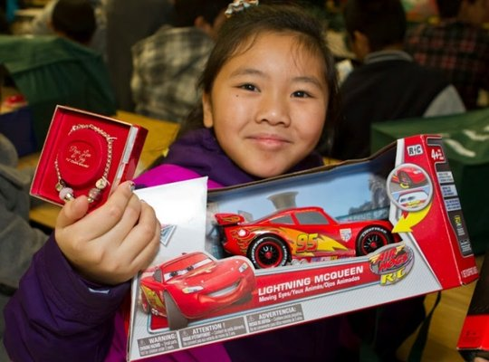 A girl proudly shows her new remote control car