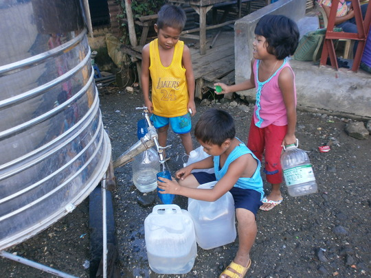 children cuing to fetch water in a rationed tank