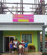Nerissa's family in front of rebuilt birth clinic