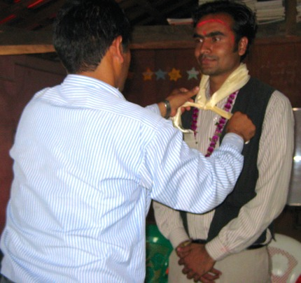 Master Trainer Bikash receiving a Malla