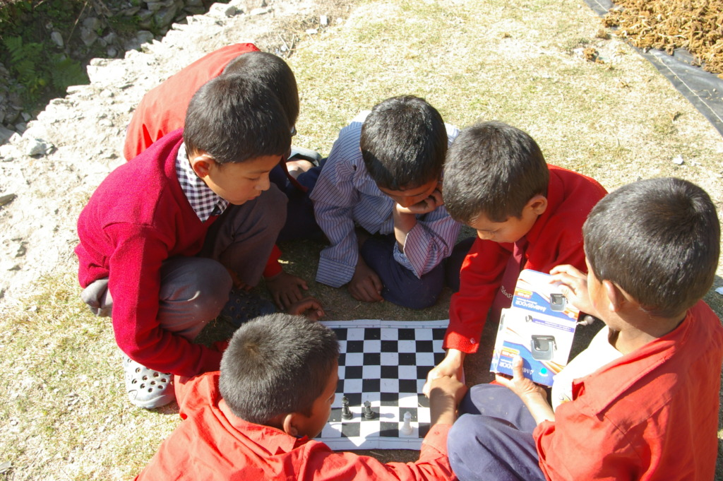 Guranse students enjoying ETC-supplied chess set